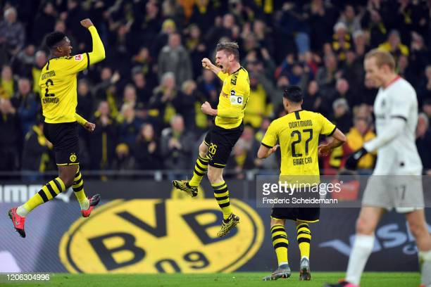 Lukas Piszczek of Dortmund celebrates his team's first goal with team mates DanAxel Zagadou and Emre Can as Sebastian Rode of Frankfurt reacts during...
