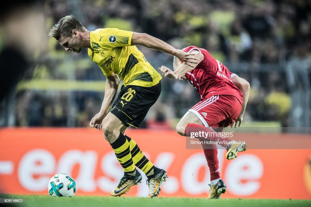 Lukas Piszczek of Dortmund is tackled by Franck Ribery of Muenchen during the DFL Supercup 2017 match between Borussia Dortmund and Bayern Muenchen at Signal Iduna Park on August 5, 2017 in Dortmund, Germany.