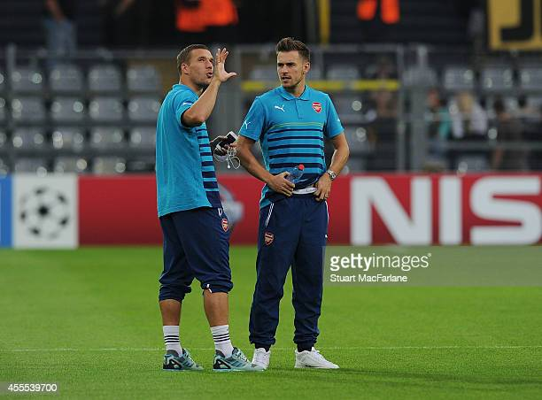 Lukas Podolski and Aaron Ramsey of Arsenal chat before the UEFA Champions League match between Borussia Dortmund and Arsenal at Signal Iduna Park on...