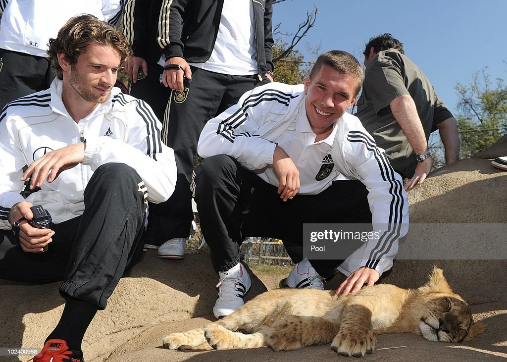 Lukas Podolski (L) and Arne Friedrich of the German National Team stroke a lion cup during a visit at the Lion Park on June 25, 2010 in Lanseria, South Africa.