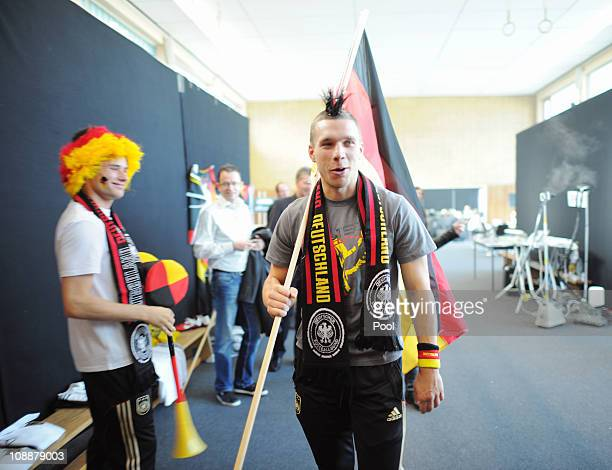 Lukas Podolski and Christian Traesch pose in fanoutfit during the German national team commercial shooting of general sponsor MercedesBenz with...