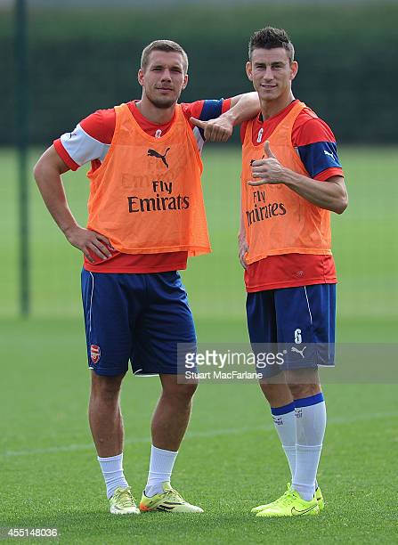 Lukas Podolski and Laurent Koscielny of Arsenal during a training session at London Colney on September 10, 2014 in St Albans, England.