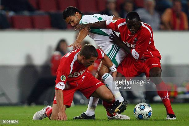 Lukas Podolski and Manasseh Ishiaku of Koeln challenge Josue of Wolfsburg during the DFB Cup second round match between 1 FC Koeln and VfL Wolfsburg...