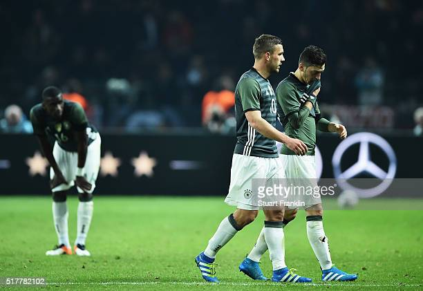 Lukas Podolski and Mesut Oezil of Germany look dejected during the international friendly match between Germany and England at Olympiastadion on...