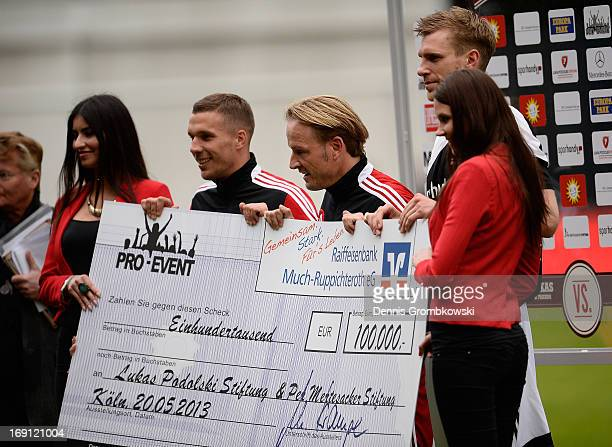 Lukas Podolski and Per Mertesacker receive a check of 100000 Euro during the Kicken fuer den guten Zweck event at Sportpark Hoehenberg on May 20 2013...