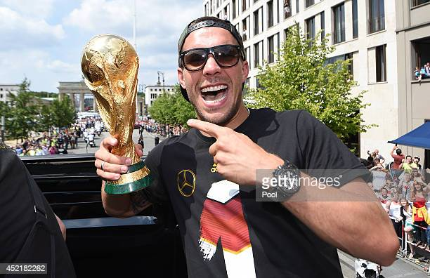 Lukas Podolski celebrates on the open top bus at the German team victory ceremony on July 15 2014 in Berlin Germany Germany won the 2014 FIFA World...