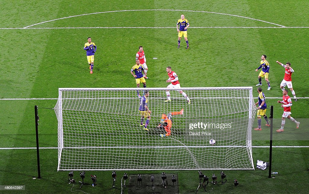 Lukas Podolski celebrates scoring Arsenal's 1st goal past Michel Vorm of Swansea during the match between Arsenal and Swansea City in the Barclays Premier League at Emirates Stadium on March 25, 2014 in London, England.