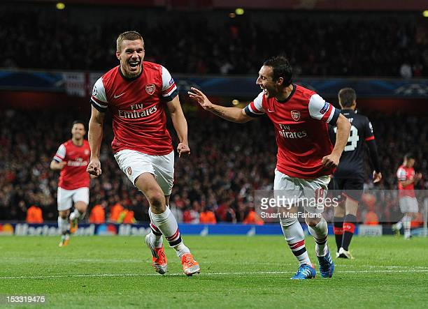 Lukas Podolski celebrates scoring the 2nd Arsenal goal with Santi Cazorla during the UEFA Champions League Group B match between Arsenal FC and...