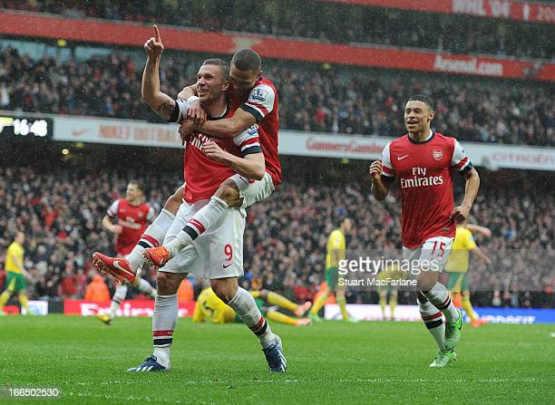 Lukas Podolski celebrates scoring the 3rd Arsenal goal with Alex OxladeChamberlain and Kieran Gibbs during the Barclays Premier League match between...