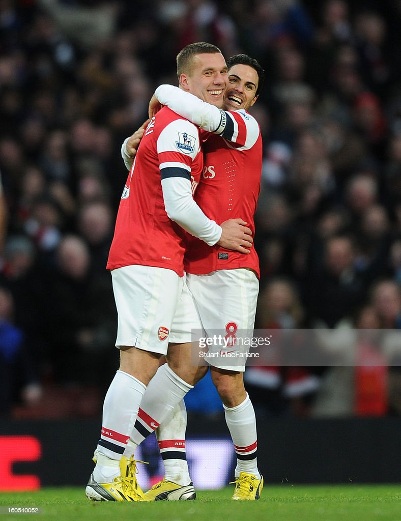Lukas Podolski (L) celebrates scoring the Arsenal goal with Mikel Arteta (R) during the Barclays Premier League match between Arsenal and Stoke City at Emirates Stadium on February 02, 2013 in London, England.