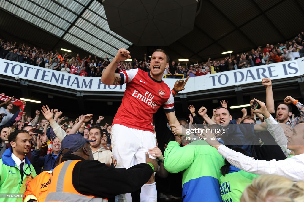 Lukas Podolski celebrates with the Arsenal fans after the Barclays Premier League match between Tottenham Hotspur and Arsenal at White Hart Lane on March 16, 2014 in London, England.