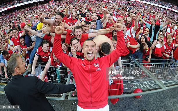 Lukas Podolski celebrates with the Arsenal fans after the FA Cup Final between Arsenal and Hull City at Wembley Stadium on May 17 2014 in London...