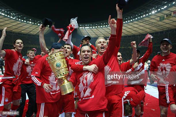 Lukas Podolski celebrating with the trophyand the team after Munich won the final of the German DFB Cup 21 in overtime against Borussia Dortmund in...