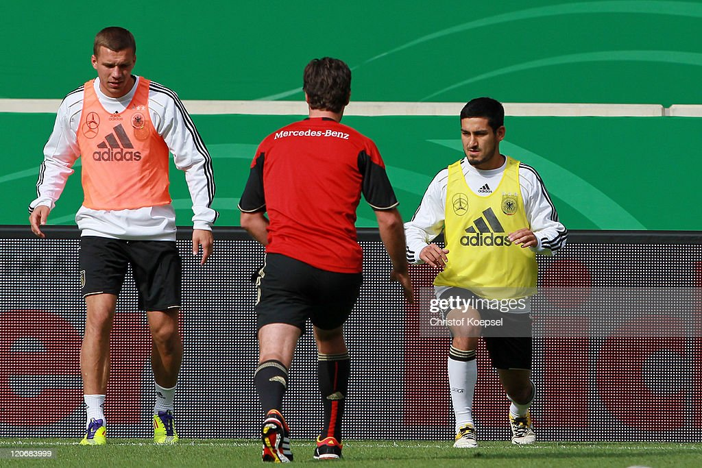 Lukas Podolski, condition coach Shad Frosythe and Ilkay Guendogan attend a training session of the German National football team at Mercedes-Benz Arena on August 8, 2011 in Stuttgart, Germany. Germany will play a friendly match against Brazil at Mercedes-Benz Arena on August 10, 2011 in Stuttgart, Germany.