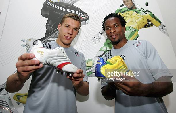 Lukas Podolski holds the boot of Germany and Jose Ze Roberto holds the boot of Brasil as they pose infront of the Adidas Tunit X32 display presenting...
