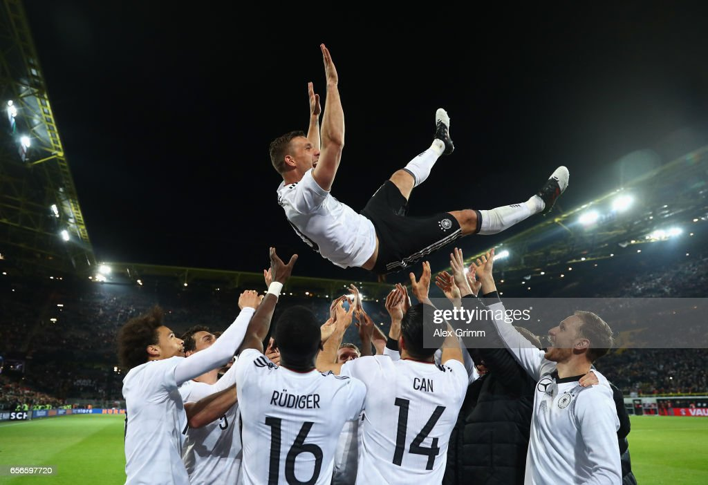 Lukas Podolski is thrown in the air by his team mates after playing his last game for Germany during the international friendly match between Germany and England at Signal Iduna Park on March 22, 2017 in Dortmund, Germany.