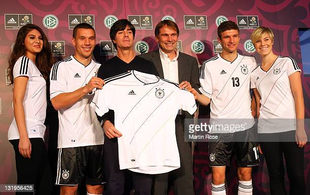 Lukas Podolski Joachim Loew Guenter Weigl of adidas and Thomas Mueller pose with the Jersey during the Germany national team Euro 2012 jersey launch...