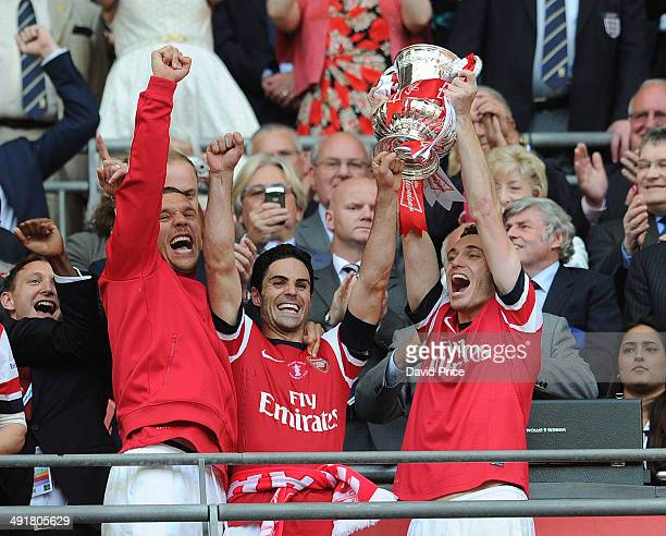 Lukas Podolski Mikel Arteta and Thomas Vermaelen of Arsenal lift the FA Cup Trophy after the match between Arsenal and Hull City in the FA Cup Final...