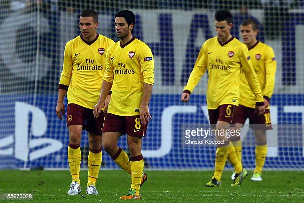 Lukas Podolski Mikel Arteta Laurent Koscielny and Jack Wilshere of Arsenal look dejected after the second goal of Schalke during the UEFA Champions...