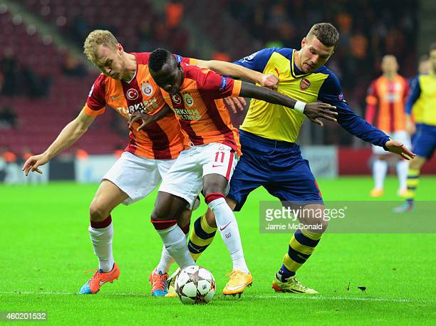 Lukas Podolski of Arsenal battles with Bruma and Semih Kaya of Galatasaray during the UEFA Champions League Group D match between Galatasaray AS and...