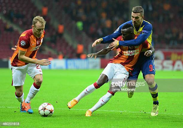 Lukas Podolski of Arsenal battles with Bruma and Semih Kaya of Galatasaray during the UEFA Champions League Group D match between Galatasaray AS and...