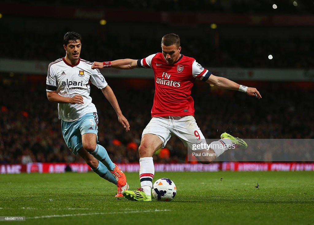 Lukas Podolski of Arsenal beats James Tomkins of West Ham United as he scores their third goal during the Barclays Premier League match between Arsenal and West Ham United at Emirates Stadium on April 15, 2014 in London, England.