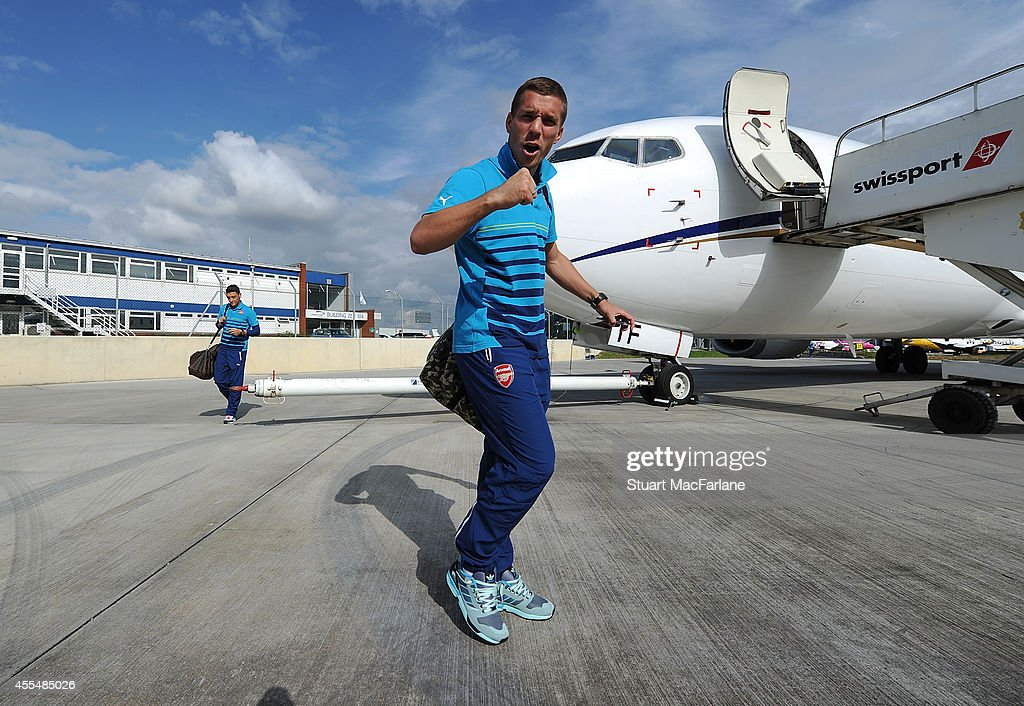 Lukas Podolski of Arsenal boards the team plane at Luton Airport on September 15, 2014 in St Albans, England. Photo by Stuart MacFarlane/Arsenal FC via Getty Images)