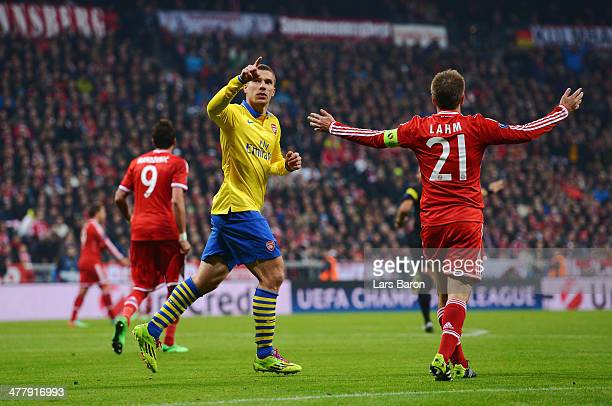 Lukas Podolski of Arsenal celebrates his goal as he goes past Philipp Lahm of Bayern Muenchen during the UEFA Champions League round of 16 second leg...