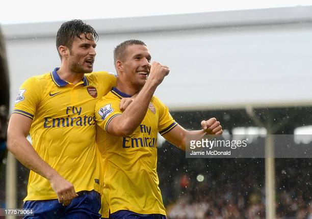 Lukas Podolski of Arsenal celebrates scoring his side's third goal with team mate Olivier Giroud during the Barclays Premier League match between...