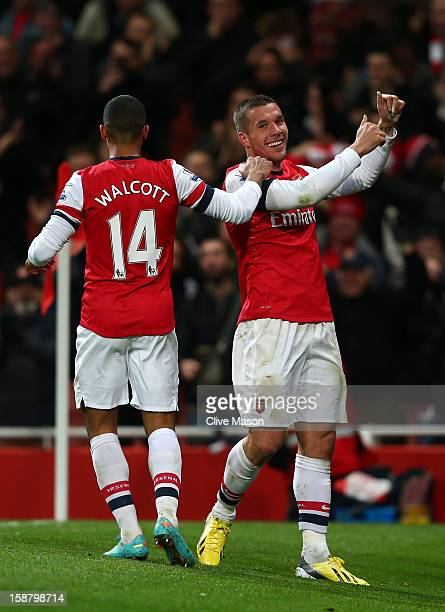 Lukas Podolski of Arsenal celebrates scoring their third goal with Theo Walcott of Arsenal during the Barclays Premier League match between Arsenal...