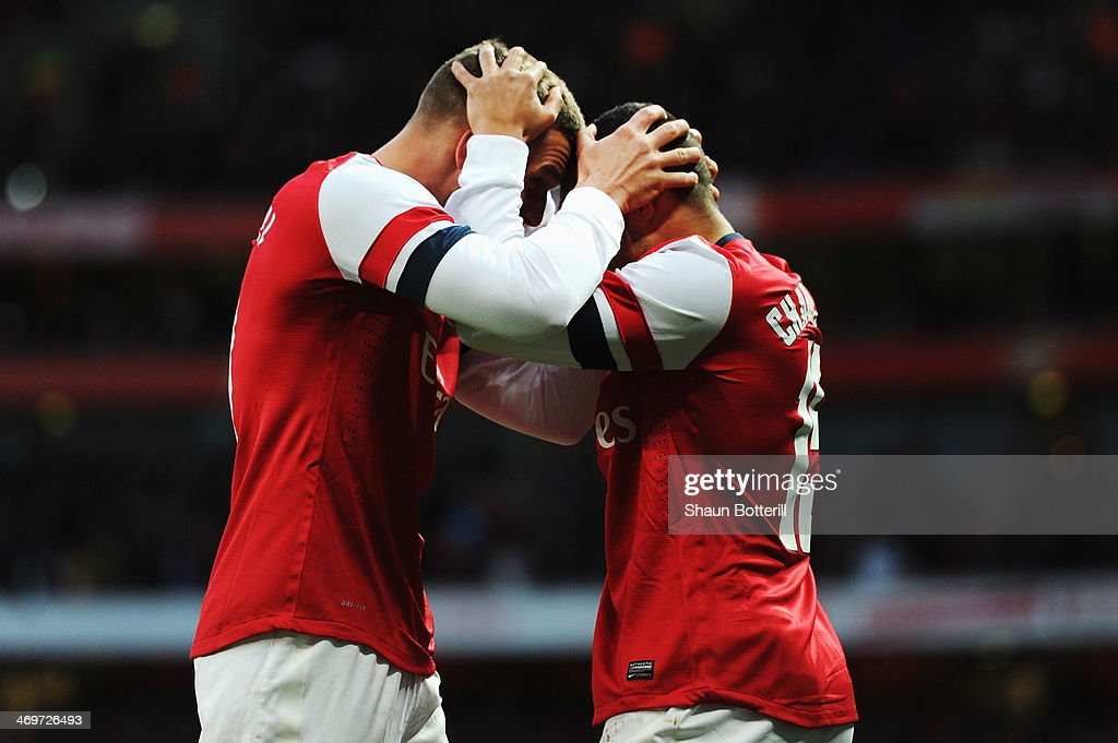 Lukas Podolski of Arsenal celebrates scoring with team mate Alex Oxlade-Chamberlain during the FA Cup Fifth Round match between Arsenal and Liverpool at the Emirates Stadium on February 16, 2014 in London, England.