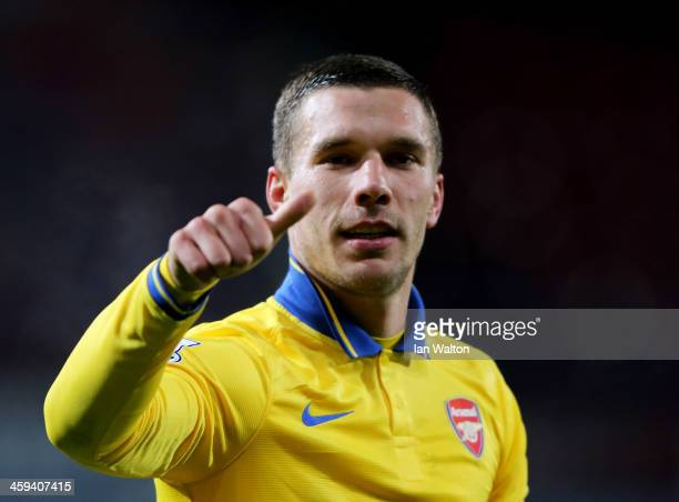 Lukas Podolski of Arsenal celebrates victory after the Barclays Premier League match between West Ham United and Arsenal at Boleyn Ground on December...