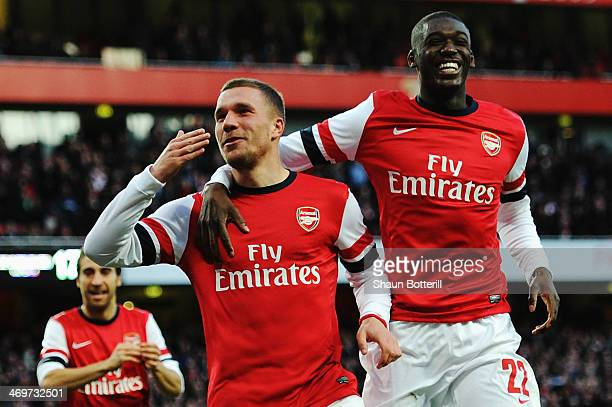 Lukas Podolski of Arsenal celebrates with team mate Yaya Sanogo after scoring during the FA Cup Fifth Round match between Arsenal and Liverpool at...