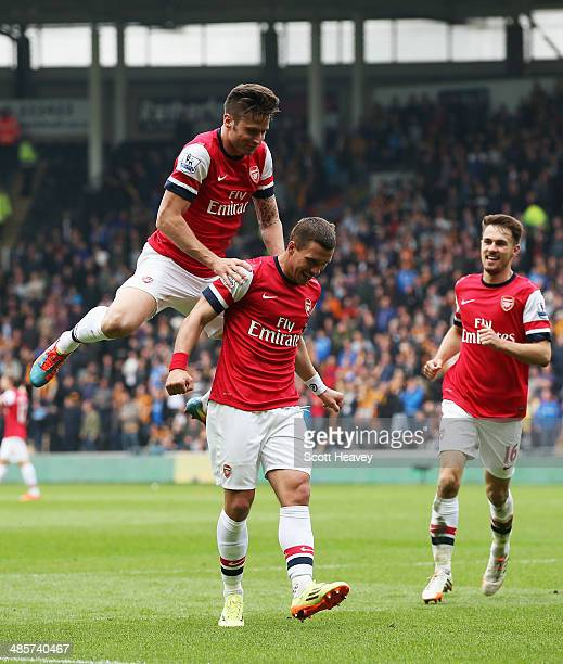 Lukas Podolski of Arsenal celebrates with team mates Olivier Giroud and Aaron Ramsey after scoring his sides second goal during the Barclays Premier...