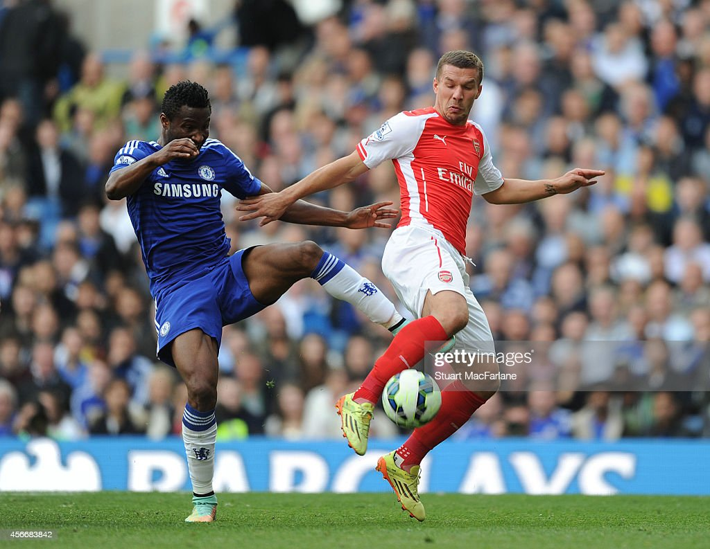 Lukas Podolski of Arsenal challenged by John Mikel Obi of Chelsea during the Barclays Premier League match between Chelsea and Arsenal at Stamford Bridge on October 5, 2014 in London, England.