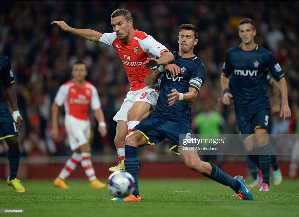 Lukas Podolski of Arsenal challenged by Jose Fonte of Southampton during the Capital One Cup Third Round match between Arsenal and Southampton at Emirates Stadium on September 23, 2014 in London, England.