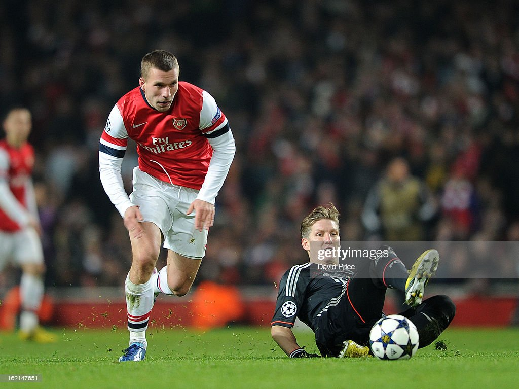 Lukas Podolski of Arsenal races past Bastian Schweinsteiger of Bayern during the UEFA Champions League Round of 16 first leg match between Arsenal FC and Bayern Muenchen at Emirates Stadium on February 19, 2013 in London, England.