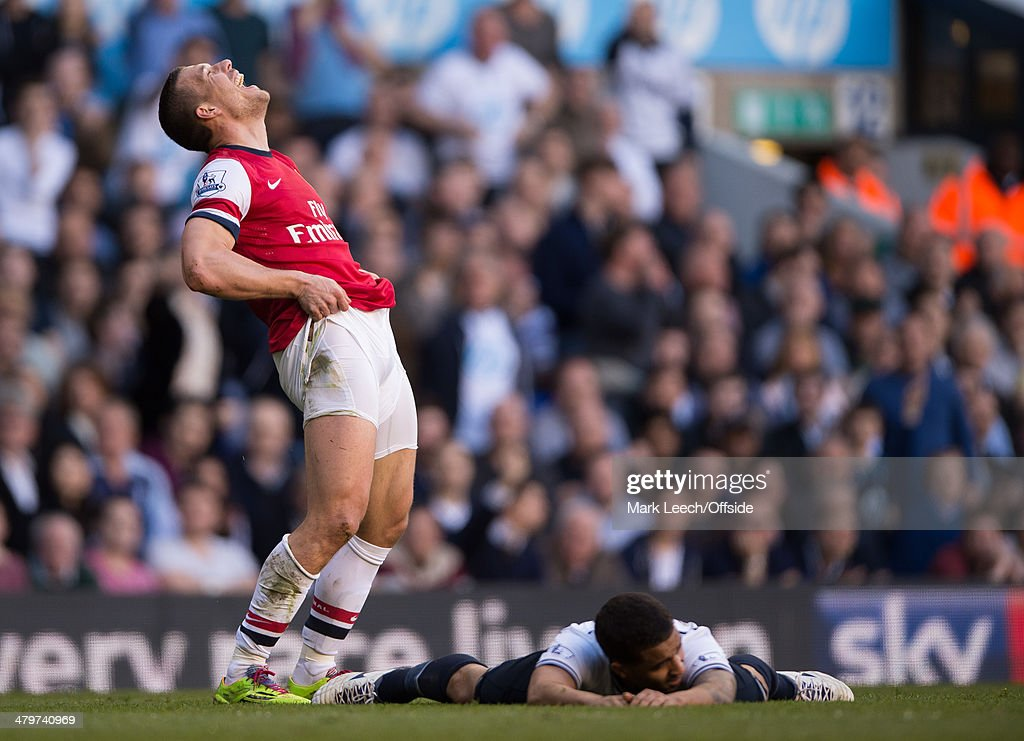 Lukas Podolski of Arsenal reacts after conceding a foal on Kyle Naughton of Tottenham Hotspur during the Premier League match between Tottenham Hotspur and Arsenal at White Hart Lane on March 16, 2014 in London, England.