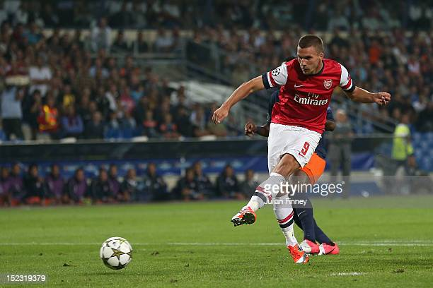Lukas Podolski of Arsenal scores his teams first goal during the UEFA Champions League match between Montpellier Herault SC and Arsenal at Stade de...