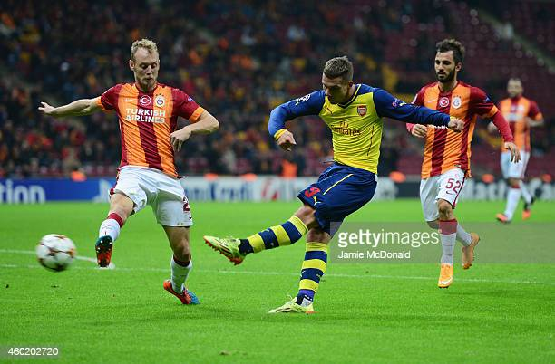 Lukas Podolski of Arsenal shoots past Semih Kaya of Galatasaray during the UEFA Champions League Group D match between Galatasaray AS and Arsenal FC...