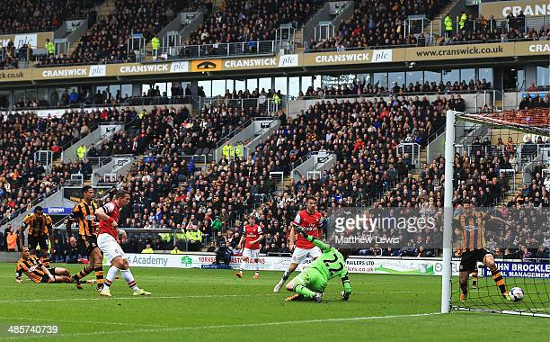 Lukas Podolski of Arsenal shoots past Steve Harper the Hull City goalkeeper to score his sides third goal during the Barclays Premier League match...