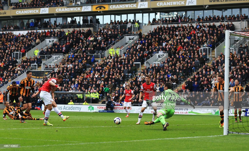 Lukas Podolski (4th left) of Arsenal shoots past Steve Harper the Hull City goalkeeper to score his sides third goal during the Barclays Premier League match between Hull City and Arsenal at KC Stadium on April 20, 2014 in Hull, England.