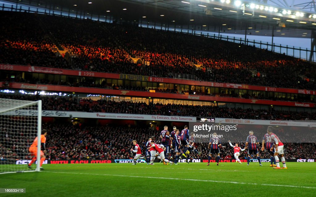 Lukas Podolski of Arsenal's free kick deflects off the wall and goes in for the first goal during the Barclays Premier League match between Arsenal and Stoke City at Emirates Stadium on February 2, 2013 in London, England.