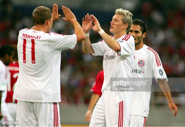 Lukas Podolski of Bayern Munich celebrates scoring with Bastian Schweinsteiger of Bayern Munich during the pre season friendly between Urawa Red...