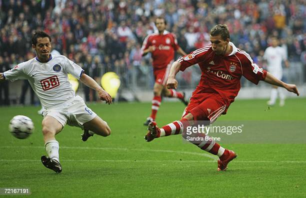 Lukas Podolski of Bayern Munich scores the sixth goal while Pal Dardai of Hertha tries to interfere during the Bundesliga match between FC Bayern...