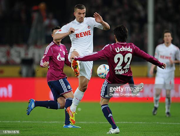 Lukas Podolski of Cologne challenges Atsuto Uchida of Schalk during the Bundesliga match between 1 FC Koeln and FC Schalke 04 at RheinEnergieStadion...