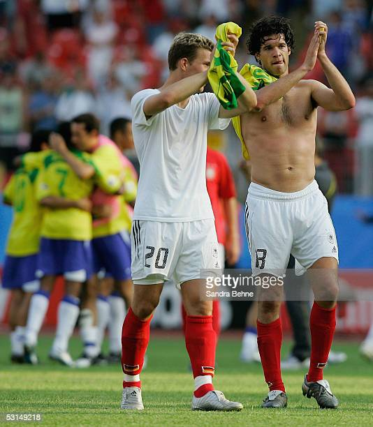 Lukas Podolski of Germany and his team mate Michael Ballack applaud the fans after losing the FIFA Confederations Cup Semi Final match between...