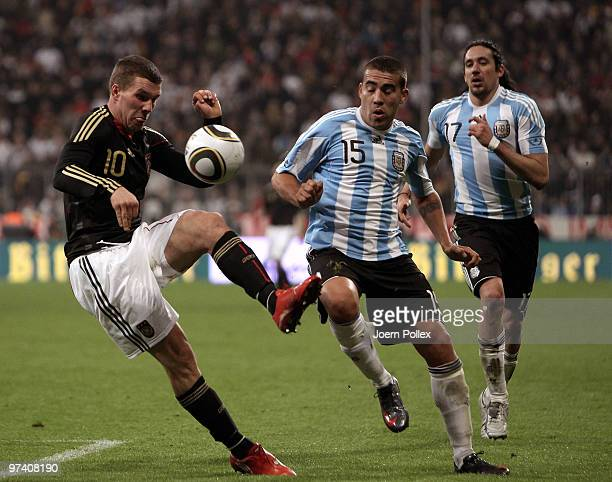 Lukas Podolski of Germany and Nicolas Otamendi of Argentina compete for the ball during the International Friendly match between Germany and...