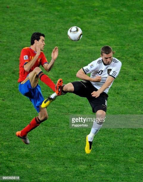 Lukas Podolski of Germany and Sergio Busquets of Spain battle for the ball during the FIFA World Cup Semi Final at the Moses Mabhida Stadium on July...