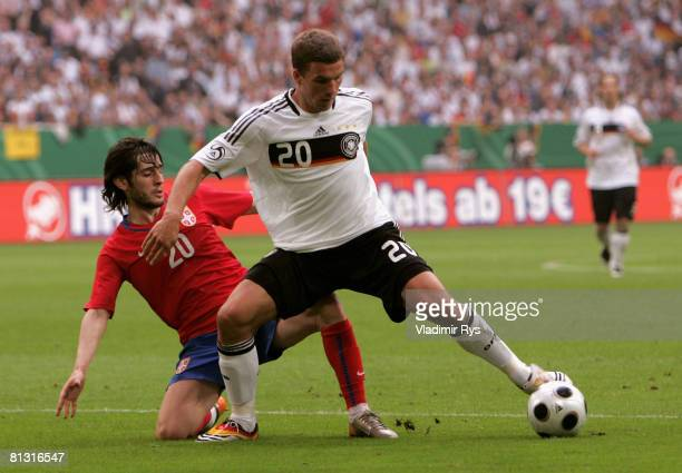 Lukas Podolski of Germany and Stefan Babovic of Serbia battle for the ball during the German international friendly match between Germany and Serbia...